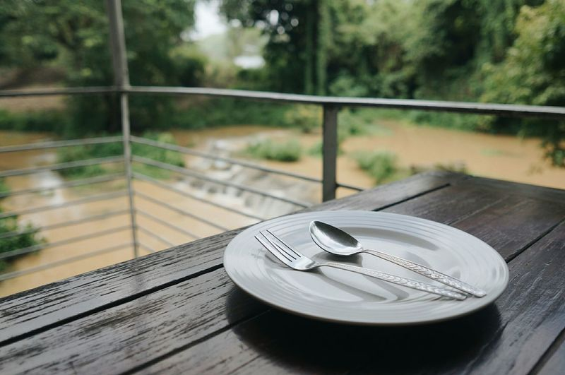 Close-up of empty plate with cutleries on wooden table in balcony
