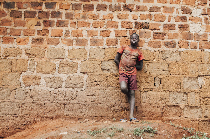 Africa African Boy Brick Brick Wall Building Building Exterior Dirt Full Length Leaning Looking At Camera One Person Outdoors People Poor  Portrait Poverty Real People Slum Slums Social Issues Street Streetphotography Village Wall