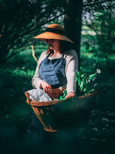 Woman wearing hat while standing in basket