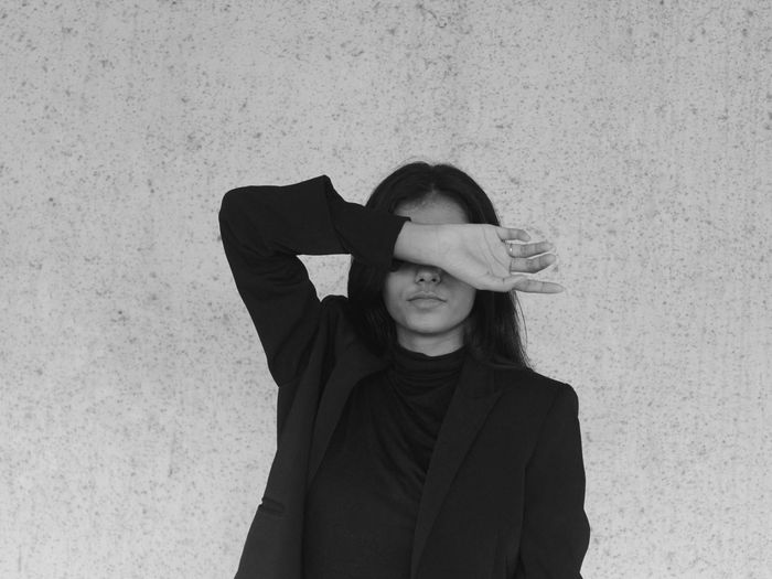 Portrait of a young woman wearing a blazer standing against wall