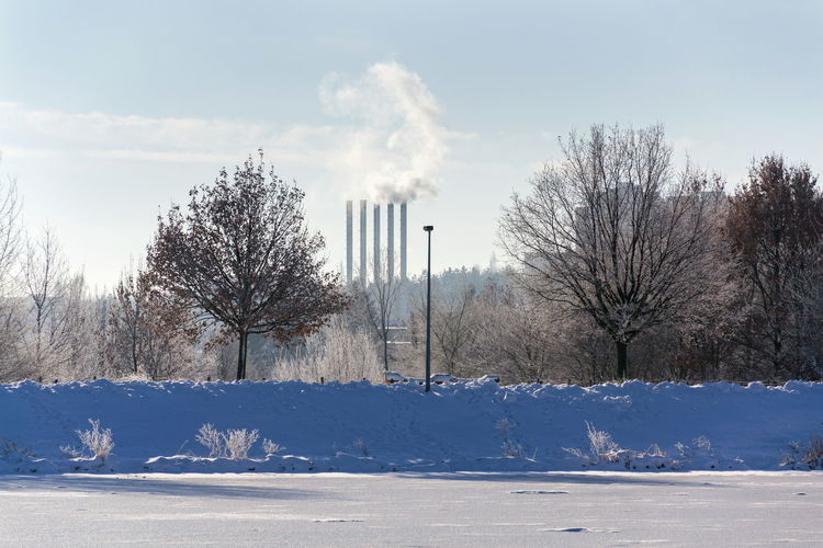 Beautiful snowy romantic winter landscape with smoking chimneys at heating plant among trees, frozen pond in foreground, sunny winter day, energy production, air pollution, climate change and global warming or freezing weather forecast concept, copy space on clear sky Cold Temperature Snow Sky Winter Tree Nature Plant Cloud - Sky No People Day Beauty In Nature White Color Outdoors Romantic Chimney Heating Plant Heating Global Warming Weather Forecast Energy Production Air Pollution Clear Sky Copy Space Ecology