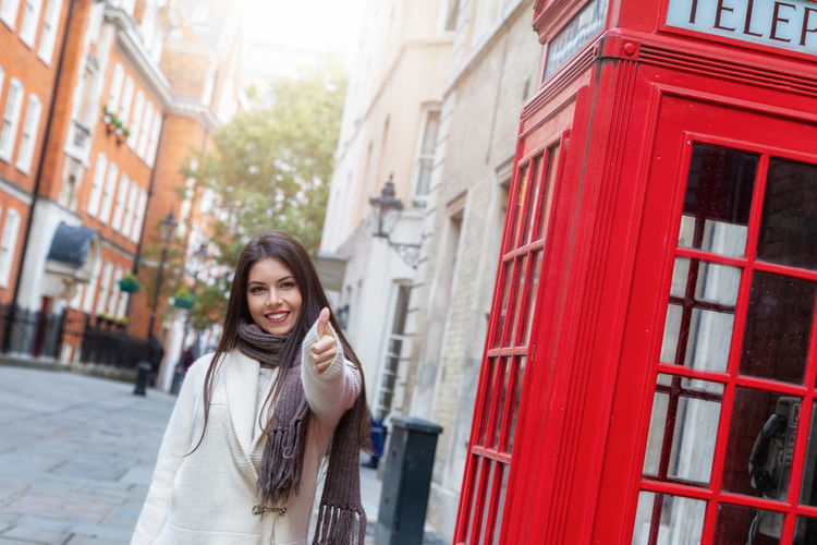 Happy London traveler woman shows the thumbs up sign next to a red telephone booth Young Adult Smiling Architecture Happiness Young Women City Beautiful Woman Building Exterior Portrait Hairstyle Telephone Lifestyles Emotion Looking At Camera One Person London Telephone Booth Red Traveler Tourist Travel Destination Urban Concept Thumbs Up