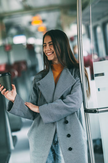 Woman holding smart phone while standing on laptop