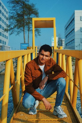 Portrait of young man crouching on footbridge in city