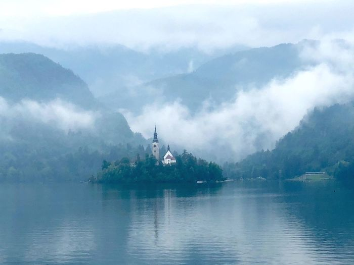 Scenic View Of Lake Bled Against Mountains During Foggy Weather