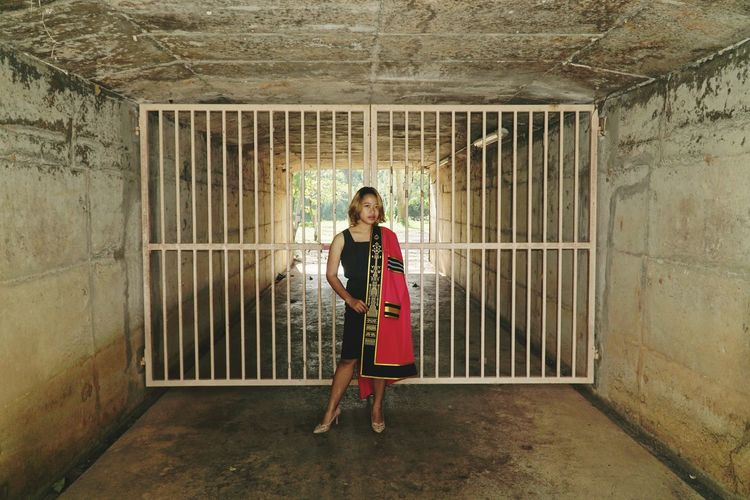 Education imprisoned, released on graduation. Tradition Gown Woman Girl Education Graduate Graduation Master Degree Full Length Smiling Cage Captivity Confined Space Posing Prison Bars Prisoner Trapped Hostage