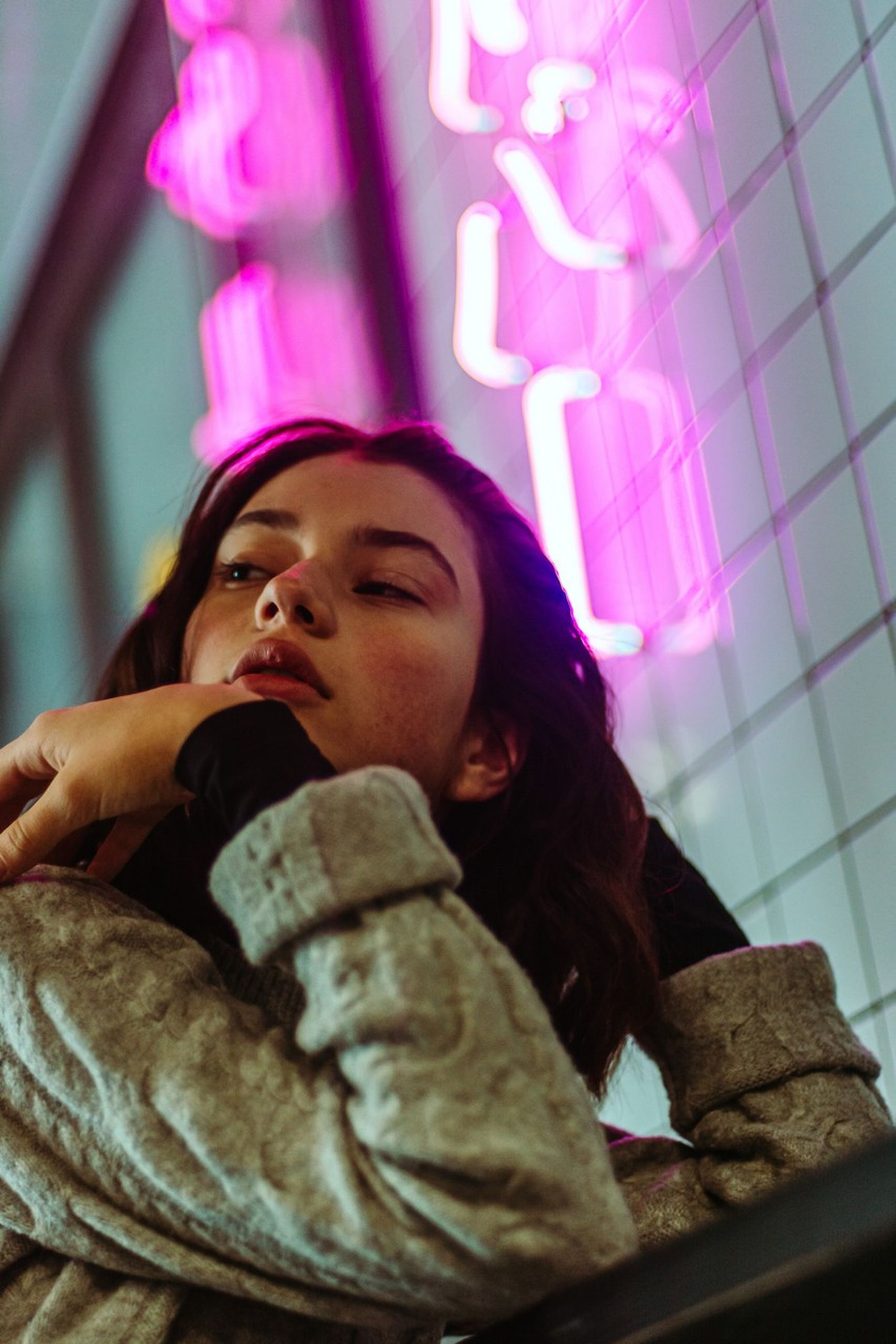 low angle view, lifestyles, real people, one person, leisure activity, women, indoors, clothing, young adult, young women, portrait, looking, pink color, headshot, casual clothing, waist up, front view, females, warm clothing, contemplation, hairstyle
