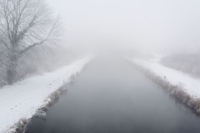 Scenic view of snow covered landscape in foggy weather