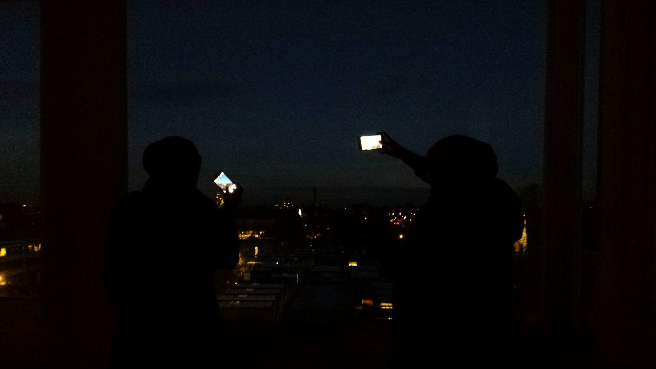 SILHOUETTE OF MEN WITH PEOPLE IN DARK