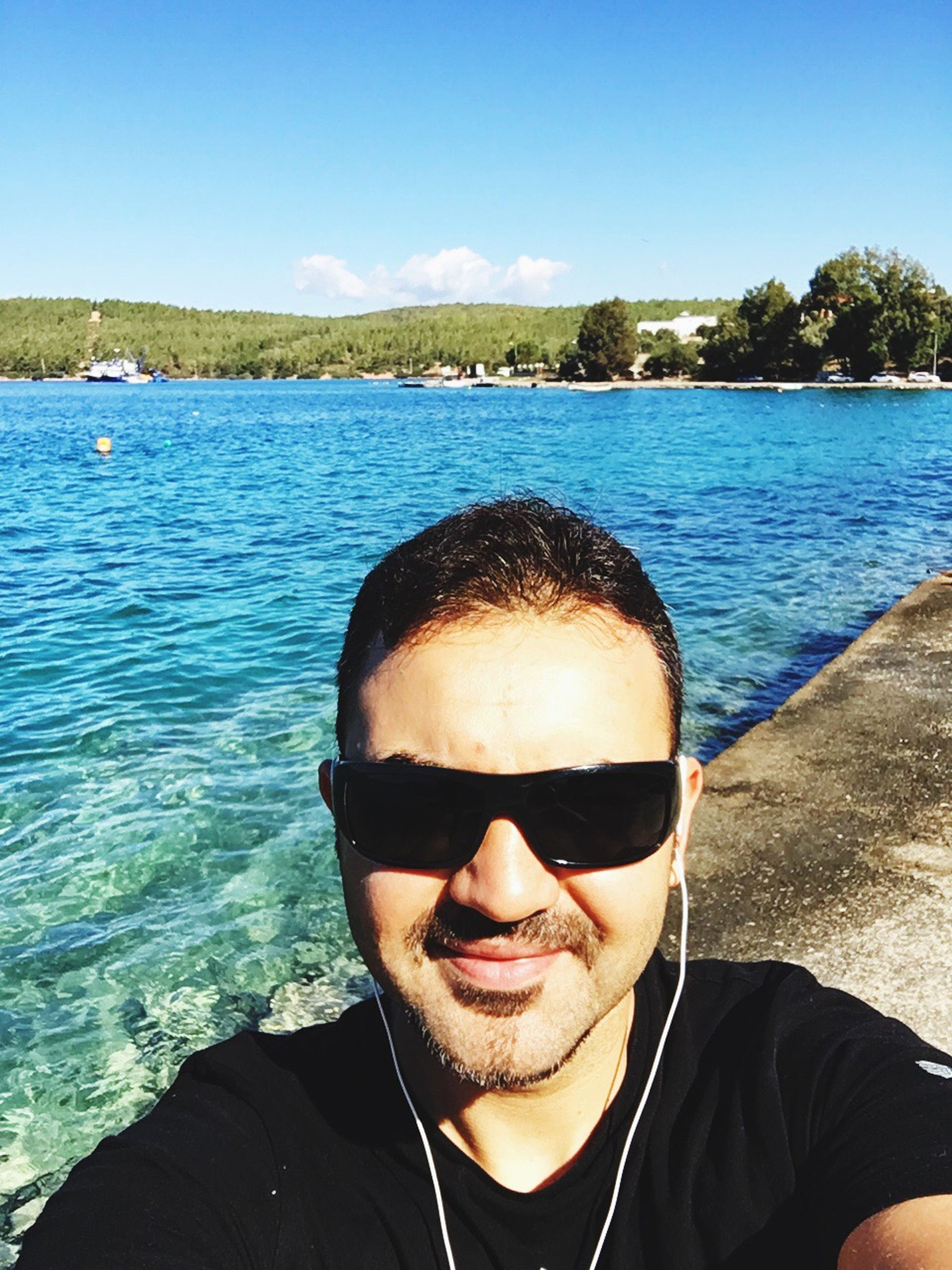 water, leisure activity, sunglasses, young men, young adult, sunlight, lifestyles, looking at camera, sky, sunny, front view, portrait, headshot, summer, person, vacations, day, blue, handsome, cloud - sky, nature, city life, human face, scenics, sea