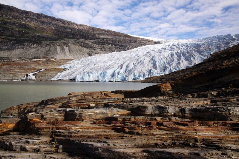 Glaciers at riverbank by mountain against sky