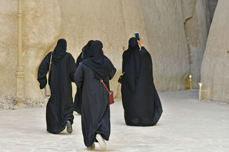 Rear view of women wearing burka against built structure