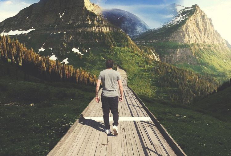 Rear view of man walking on boardwalk against mountains