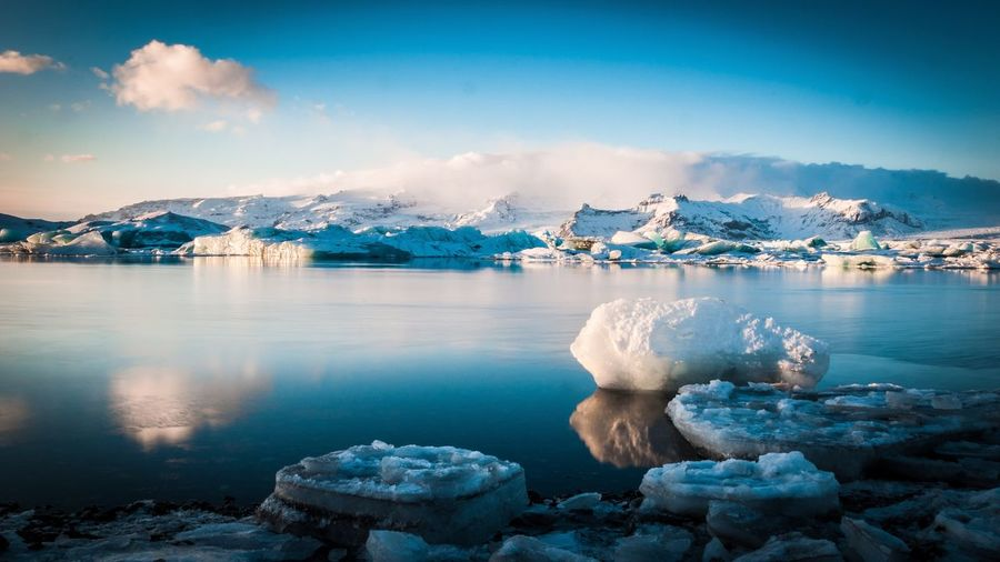 Scenic view of icebergs at lakeshore by snowcapped mountains against sky