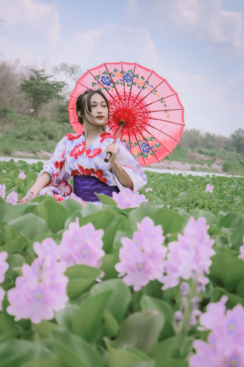 Low angle view of woman holding flowering plants against sky