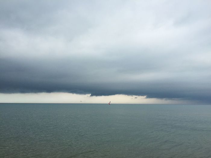 Sailboat sailing in lake with dark, storm clouds surrounding it. Sailboat Sailing Sail Lake Lake Michigan Water Dark Clouds Dark Storm Storm Clouds Bad Weather