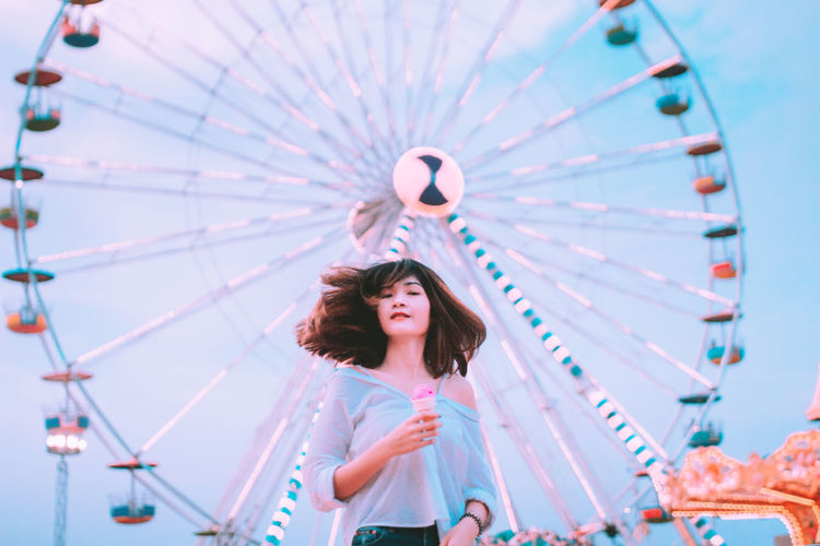 Low angle view of woman looking at amusement park