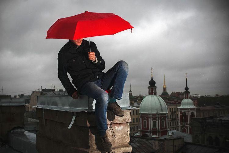 Man Holding Red Umbrella Sitting On Roof