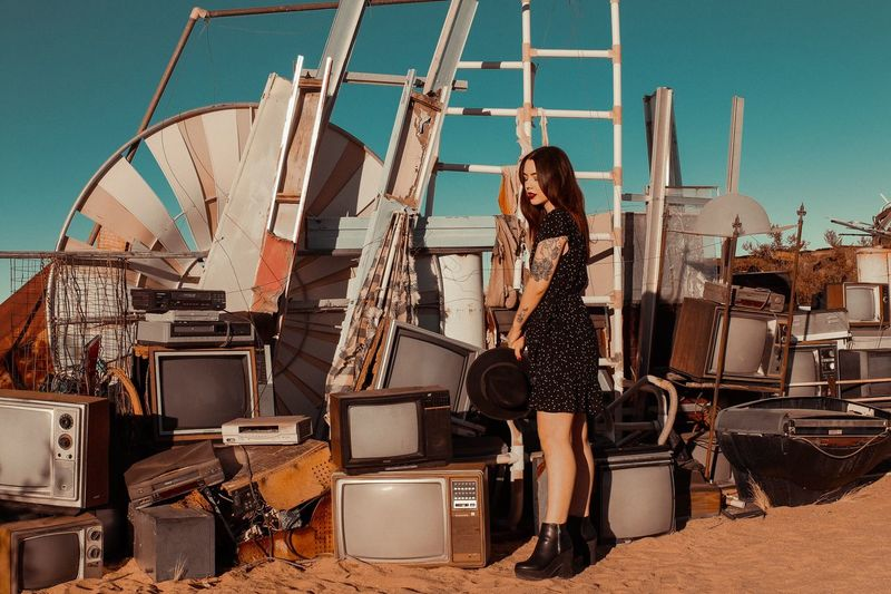 Side view of beautiful young woman standing at junkyard