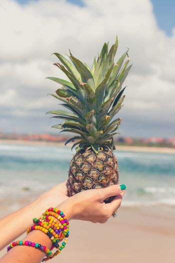 Hands of woman holding pineapple at beach against sky