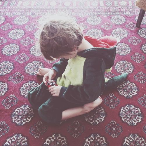 High angle view of boy sitting on carpet