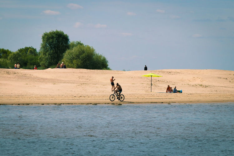 People riding on beach against sky