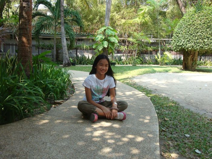 Portrait of smiling girl sitting on footpath at park