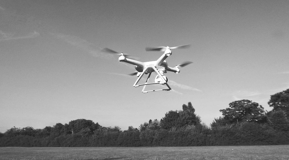 Flying Mid-air Clear Sky Day Motion Tree Air Vehicle Outdoors Technology Aerospace Industry Airplane Airshow No People A Kid With A New Toy Drone  New Toy Media Equipment Playtime Monochrome Black And White Mi Drone Xiaomi Hovering Drone Shot Drone
