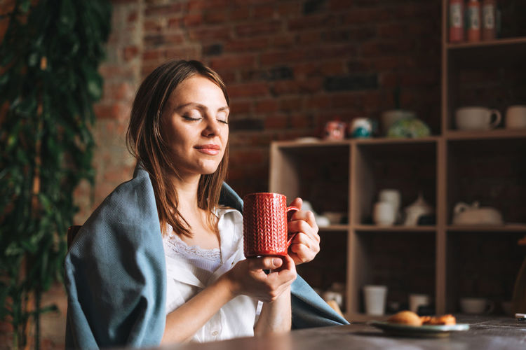 Young woman in cozy grey scarf with mug of tea in hands looks out the window and rests in studio
