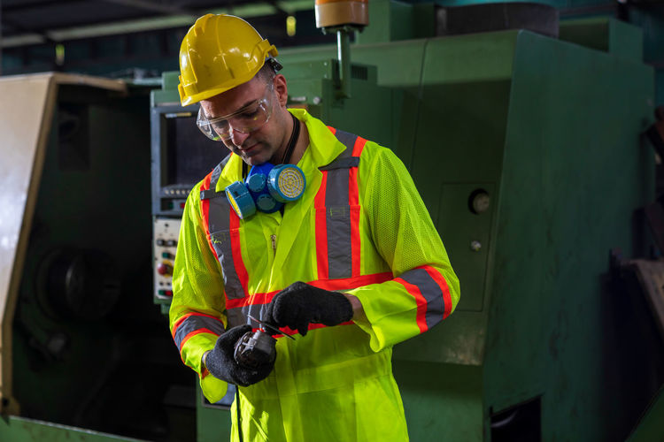 Professional technicians wearing safety clothing are servicing machinery in an industrial factory.