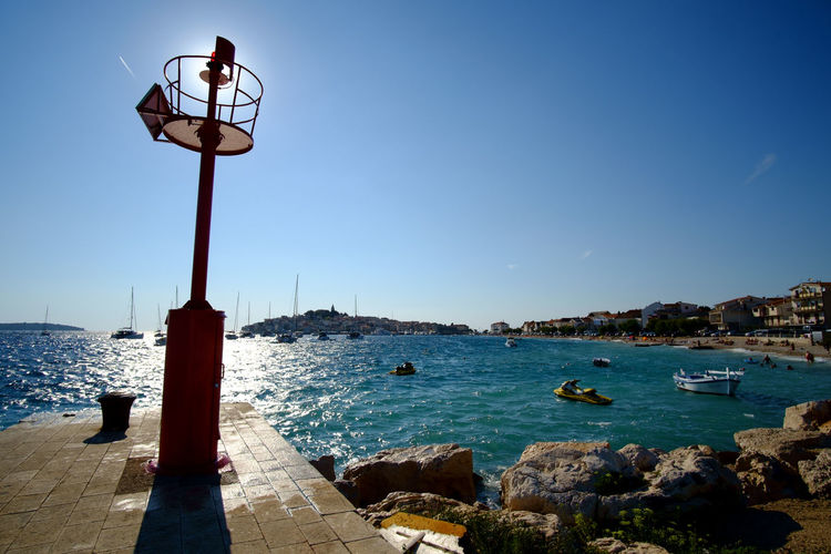 Primosten, Croatia Primošten Animal Themes Beauty In Nature Blue Clear Sky Day Nature No People Outdoors Perching Rock - Object Sea Sky Street Light Water