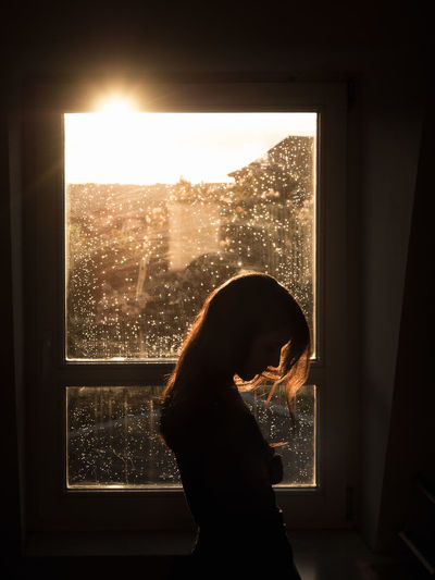 Side view of silhouette woman looking through window