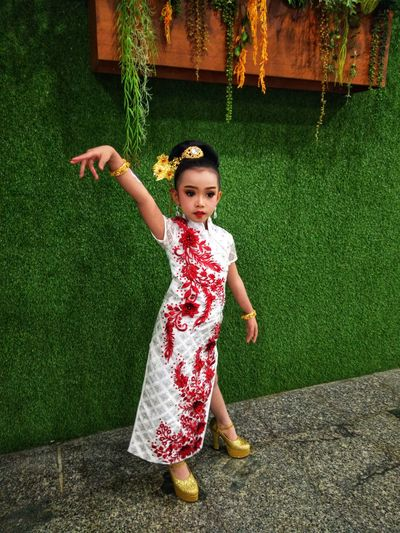 Chinese New Year model girl with Kipao suit, Chinese style Girl Model Asian Girl Asian Girl Model Thai Girl Chinese New Year Chinese Suit Chinese Style Child Childhood Full Length Girls Playing Front Or Back Yard Standing Grass Garden Hose