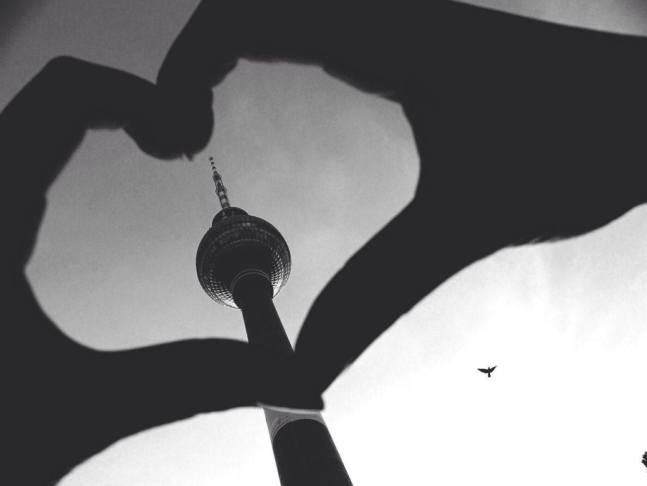 Silhouette hands forming heart shape against tower