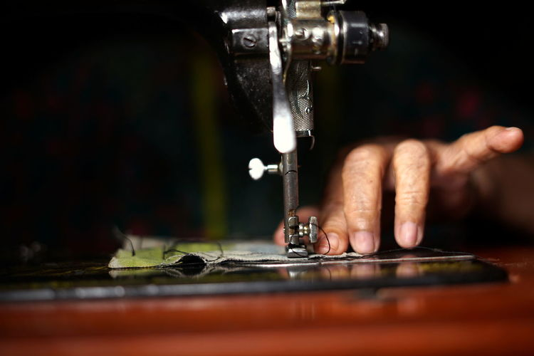 Cropped hand of person working on sewing machine