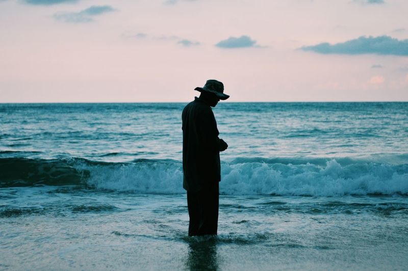Side View Of Man Standing At Beach