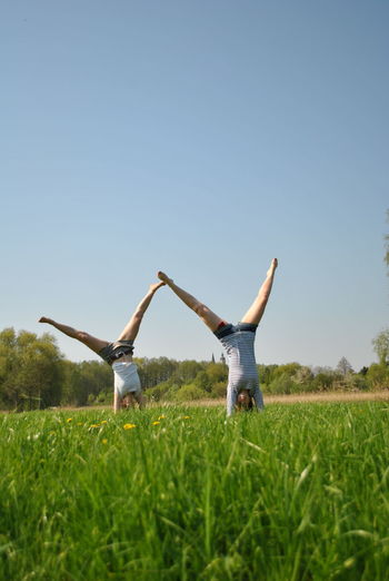Friends doing handstand on field against sky