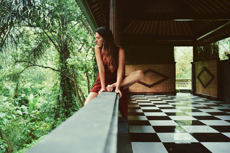 Young woman sitting on retaining wall over tiled floor