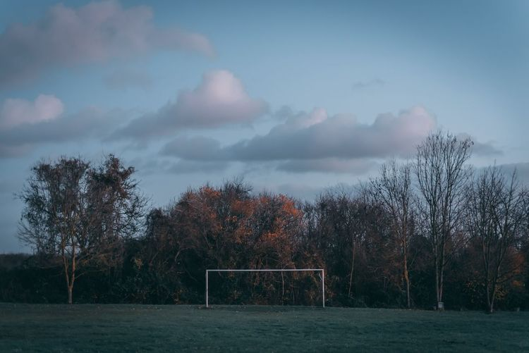 Trees and soccer goal on field against sky at sunset