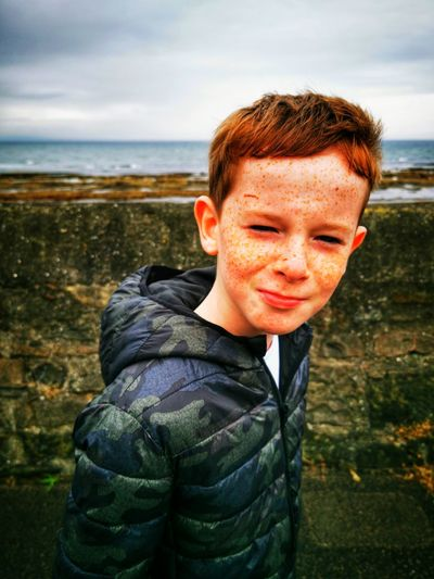 Portrait of boy with freckles on face against sea
