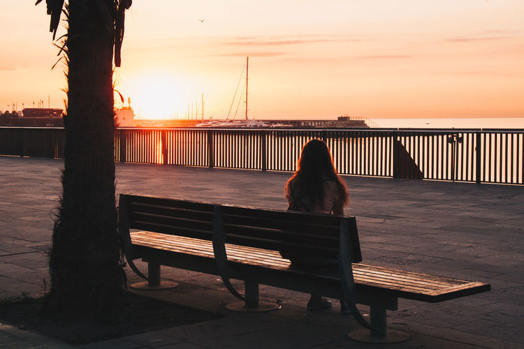 Rear View Of Silhouette Woman Sitting On Bench