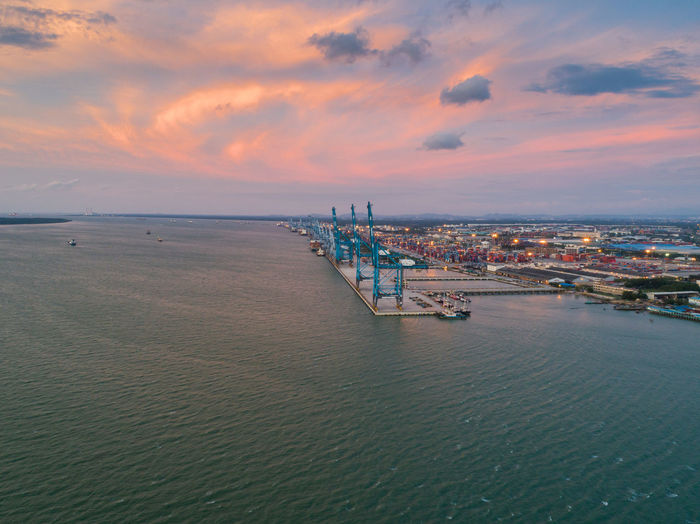 Heavy duty crane at port area with scenic sunset Sky Water Sea Sunset Cloud - Sky Architecture Built Structure Building Exterior Waterfront Nature Scenics - Nature City Beauty In Nature No People Nautical Vessel Transportation Bridge Orange Color Horizon Outdoors Horizon Over Water Cityscape