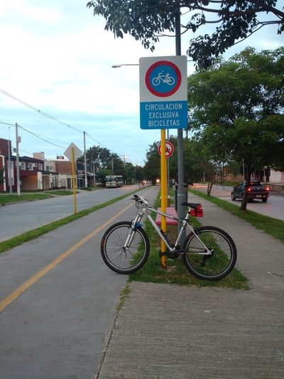 Bicycle sign on road in city against sky