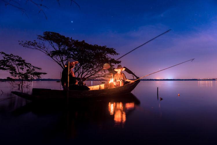 People fishing in lake at dusk