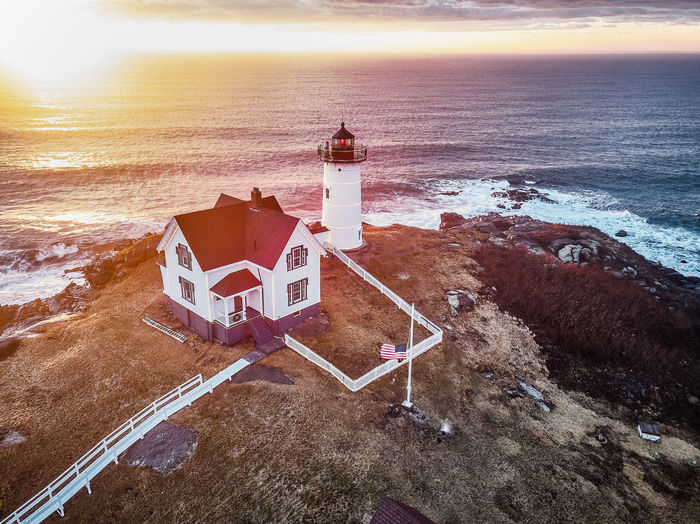 High Angle View Of Lighthouse On Beach By Sea Against Sky