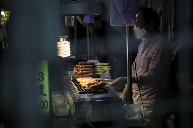 Man preparing sausages on barbecue grill in market