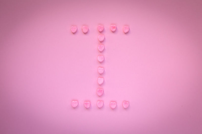 Close-up of heart shape candies over pink background