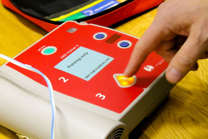 A finger pressing a button of a training defibrillator in an exercise Body Part Close-up Defibrillator Finger Hand Human Body Part Human Finger Human Hand Indoors  One Person Real People Red Training Western Script