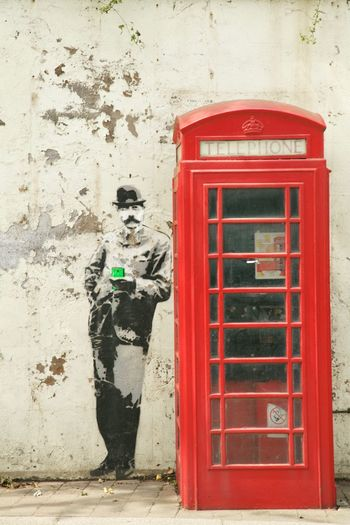 Banksy-style art of Sir Edward Elgar, holding a smartphone, standing next to a typical old-fashioned red British phonebox. This is located in Malvern, near Worcester, where Elgar spent a lot of his life. Elgar Humor Malvern Malvern Hills Banksystyle Communication Edwardelgar Full Length Humor 😂😂😂😂 Humourous Pay Phone Red Redphonebox Smart Phone Technology Telephone Telephone Booth