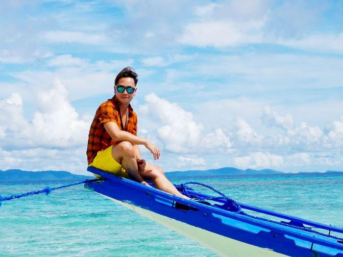 Man sitting on boat in sea against sky